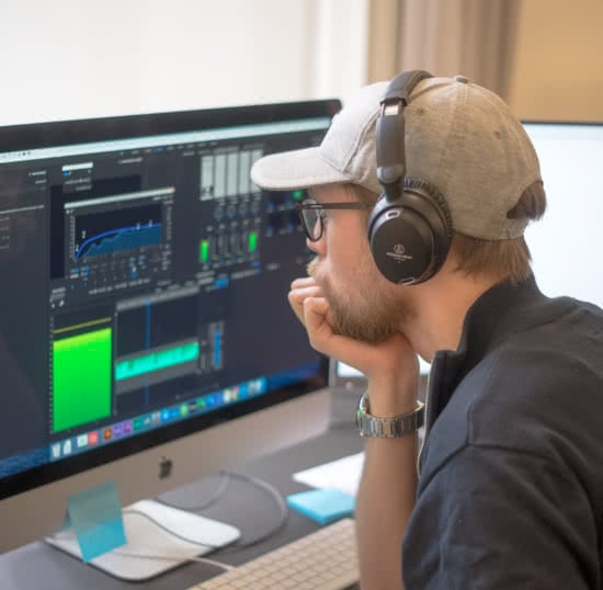Morten wearing headphones working in Premiere Pro