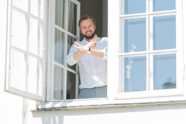 Our CEO standing in window smiling